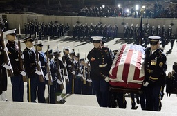 A military honor guard carries the casket of former President Gerald Ford up the steps of the U.S. House of Representatives in Washington