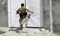 A Kurdish gunman kicks a door as he searches for Shi'ite militiamen during clashes in Tuz Khurmato