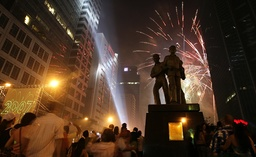 Filipinos watch a fireworks display during New Year celebrations in Manila's Makati financial district