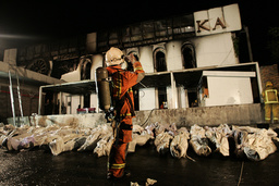 A Thai fire official takes a picture of the bodies of victims outside Santika nightclub in Bangkok