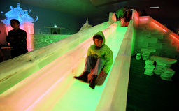 YOUNG BOY SLIDES DOWN ICE RAMP AT THE SNOW AND ICE CITY EXHIBITION IN SYDNEY