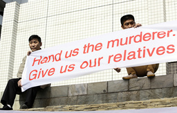Family members of passengers onboard the Malaysia Airlines Flight MH370 hold a banner during a protest in Beijing