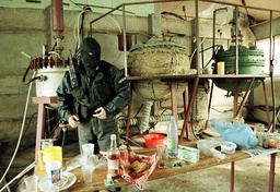 A MASKED POLICEMAN CHECKS ILLEGAL DRUG FACTORY IN BULGARIA