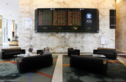 A couple talk near indicator board at the Australian Securities Exchange in Melbourne