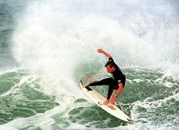 TAI BURROW NEGOTIATES A WAVE DURING A SURFING COMPETITION