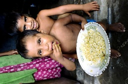 A CHILD EATS RICE IN A FLOOD SHELTER IN DHAKA