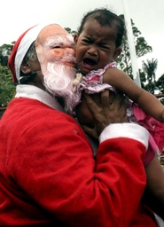 East Timorese President Xanana Gusmao, wearing a Santa Claus costume, kisses a child during the celebration of Christmas at his home in Balibar