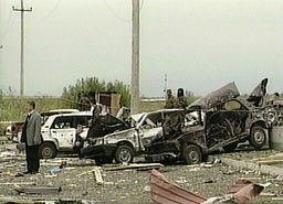 BURNT OUT WRECKAGE OF CARS ARE SEEN IN STREET FOLLOWING BLAST AT MAGAS