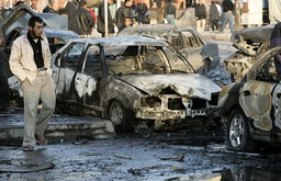 A man walks past burnt vehicles at the scene of a car bomb attack in Baghdad