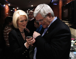 U.S. Republican presidential candidate Gingrich and his wife Callista look at a photograph on her phones on his campaign bus after a stop in Waterloo