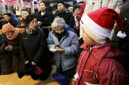 People pray during a mass to celebrate Christmas in Shenyang