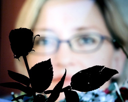 PORTRAIT OF ANNA LINDH IS SEEN AMONG FLOWERS OUTSIDE THE NK STORE IN STOCKHOLM WHERE THE SWEDISH FOREIGN MINISTER WAS STABBED WHILE THE OFFICIAL MEMORIAL SERVICE TAKES PLACE IN THE CITYHALL OF STOCKHOLM SEPTEMBER 19, 2003.