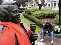 James Brown fan sits on park bench near statue of singer in Augusta