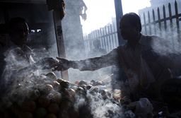 A fruit vendor and his customer are enveloped in incense smoke in Mumbai