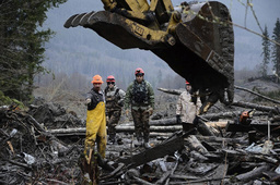 Washington National Guard personnel join civilian workers to find missing persons following a deadly mudslide in Oso