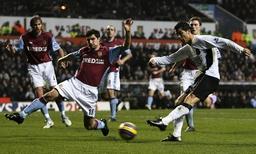 Manchester United's Ronaldo shoots past Aston Villa's Hughes during their English Premier League match in Birmingham