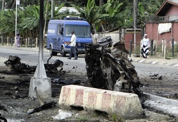 People walk past the wreckage from a car bomb explosion in Port Harcourt, Nigeria