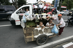 A food seller pushes her cart at a street in Surabaya, Indonesia