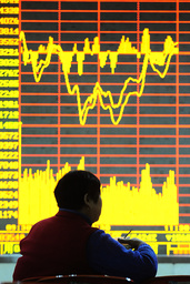 An investor sits in front of an electronic board showing stock information at a brokerage house in Hefei