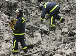Firemen inspect the rubble at one of the parking lots of Madrid's Barajas airport