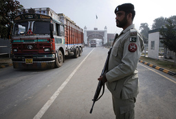 A paramilitary soldier stands guard as a truck crosses into Pakistan from India at the Wagah border