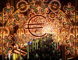 SHOPPERS STROLL UNDER CHRISTMAS LIGHTING WITH EURO LOGO ON RUE MONTORGUEIL IN PARIS