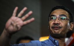 Malaysia's acting Transport Minister Hishammuddin Hussein gestures as he speaks about search for missing Malaysia Airlines Flight MH370, during a news conference in Putrajaya