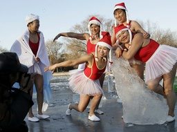 People dressed in Santa Claus costumes take a photo at a park in Shenyang