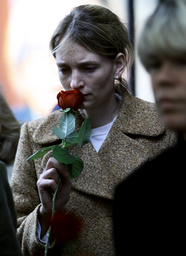 WOMAN STANDS WITH SINGLE ROSE OUTSIDE THE NK STORE IN STOCKHOLM WHERE THE SWEDISH FOREIGN MINISTER WAS STABBED WHILE THE OFFICIAL MEMORIAL SERVICE TAKES PLACE IN THE CITYHALL OF STOCKHOLM SEPTEMBER 19, 2003.