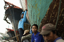 A daily-rated port worker yawns next to a traditional Phinisi wooden boat as he waits for customers at Sunda Kelapa port in Jakarta