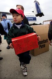 CHILD HOLDS GIFT TO BE LOADED ON AIRLIFT FOR ARGHANISTAN CHILDREN