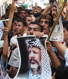 PALESTINIAN DEMONSTRATORS CARRY A POSTER OF PALESTINIAN PRESIDENT YASSER ARAFAT DURING A DEMONSTARTION TO SUPPORT HIM IN HEBRON