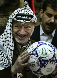 PALESTINIAN PRESIDENT YASSER ARAFAT HOLDS A BALL RECEIVED BY AN ITALIAN DELEGATION DURING A MEETING AT HIS HEADQUARTERS IN RAMALLAH