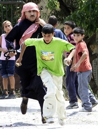 A PALESTINIAN TRIES TO STOP A BOY THROWING STONES IN BETHLEHEM