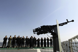 Military personnel pray as they stand behind cleric on naval ship during Velayat-90 war game on Sea of Oman near Strait of Hormuz in southern Iran