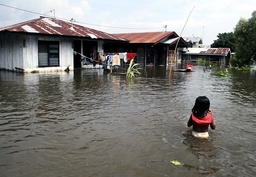 A child walks through floodwaters in the district of Kampar