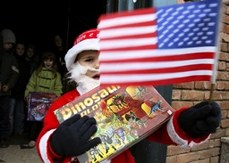 A Kosovo child waves a U.S. flag after he received Christmas presents from U.S. Marine Corps in Djakovica