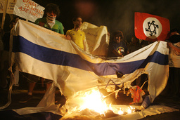 Protesters burn an Israeli flag during demonstrations against the bombing of the Gaza Strip outside Israel's embassy in Lima