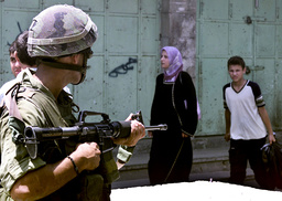 AN ISRAELI SOLDIER POINTS HIS RIFLE AT A PALESTINIAN IN HEBRON