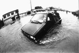 A CHINESE MAN PUSHES A CAR THROUGH A FLOODED STREET