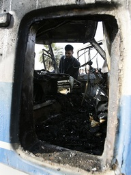 A man looks inside a burnt bus after a suicide bomb attack in Baghdad