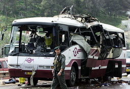 AN ISRAELI SOLDIER GUARDS THE WRECKAGE OF A BUS WHICH WAS DESTROYED BY AN EXPLOSION NEAR UMM AL-FAHM