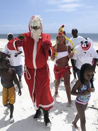 Man dressed as Santa Claus walks on the beach of the port city of Mombassa