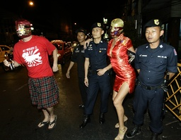 Tourists pose with Thai police at Khao San road in Bangkok