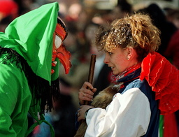 A GIRL LOOKS FACES A WITCH AT A CARNIVAL PARADE IN GERMANY