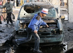 A youth walks past a damaged vehicle after a car bomb attack in Baghdad