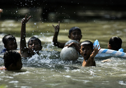 Children play in a river during their Christmas holiday in Karawang district