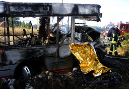 A GERMAN FIRE FIGHTER WALKS PAST THE REMAINS OF A BURNT OUT BUS IN THE WESTEREN GERMAN TOWN OF GREFFERN