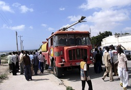 Residents inspect a fire engine damaged during an Ethiopian air strike at Mogadishu's international airport