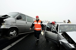 Rescue workers walk between cars after pile up involving fifty vehicles on French motorway in direction of Bordeaux to Bayonne, southwestern France